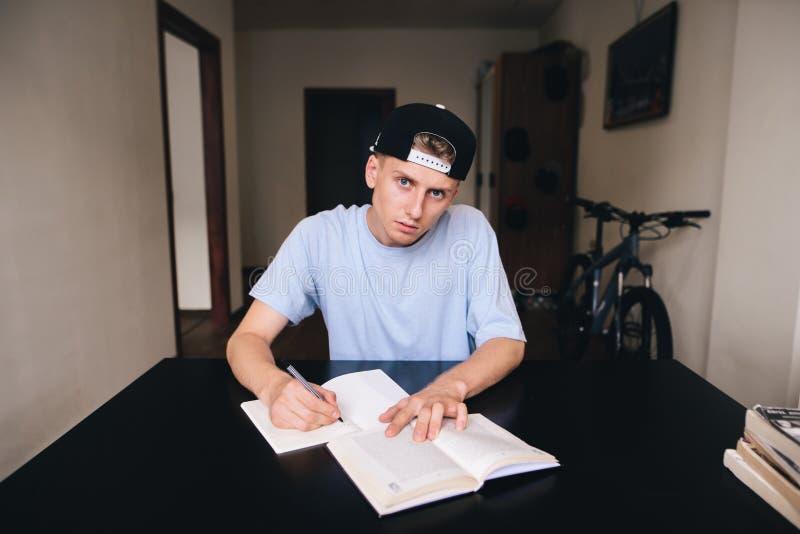 Nastoletni robi pracie domowej podczas gdy siedzący w jego pokoju Spojrzenie przy kamerą zdjęcie royalty free