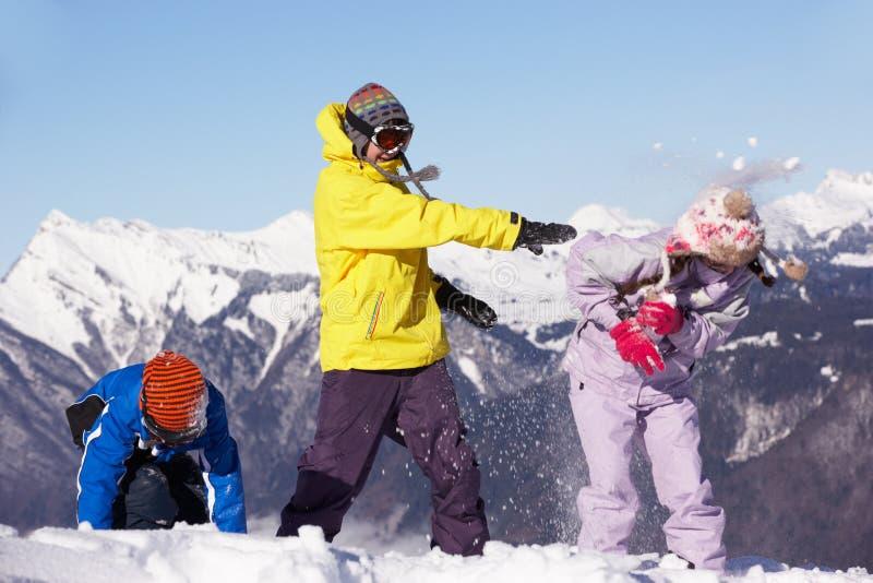 Nastoletni Rodzinny Mieć Śnieżną Walkę W Górach obrazy royalty free