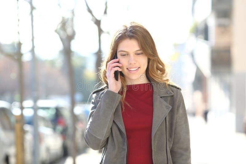 Nastoletni spacery opowiada na m?drze telefonie w ulicie obrazy stock