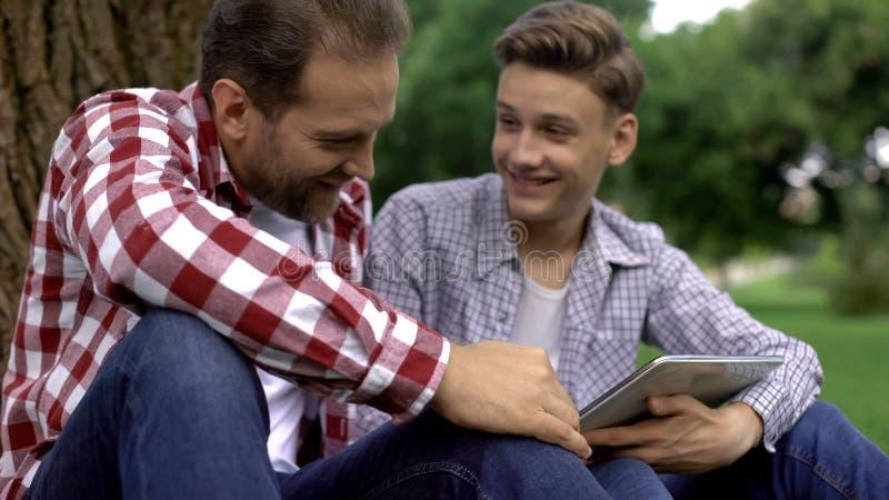 Nastoletni syn pokazuje fotografie jego dziewczyna ojciec, mężczyzna rozmowy, zaufań powiązania zdjęcie stock