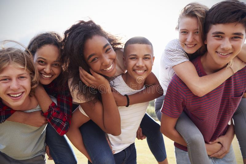 Nastoletni szkolni przyjaciele ma zabawę piggybacking outdoors zdjęcia royalty free