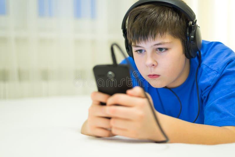 Nastoletni używa telefon komórkowy z hełmofonami fotografia royalty free