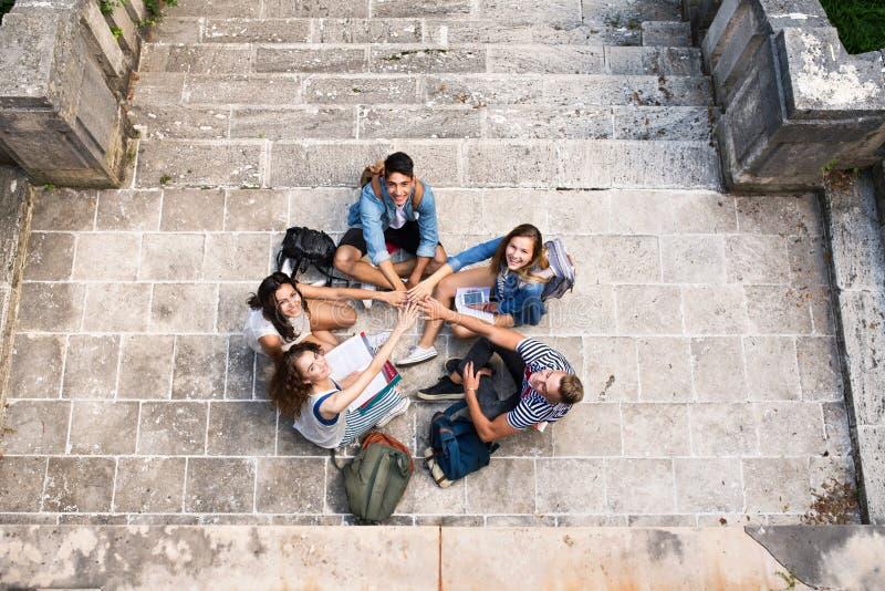 Nastoletni ucznie przy kamiennymi krokami przed uniwersytetem obraz stock
