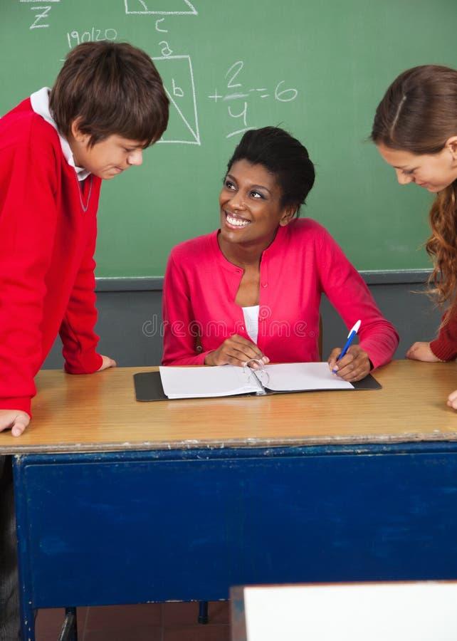 Nastoletni ucznie Z nauczycielem Przy biurkiem W sala lekcyjnej obraz royalty free