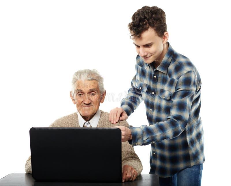 Nastoletni z jego dziadkiem przy laptopem zdjęcia royalty free