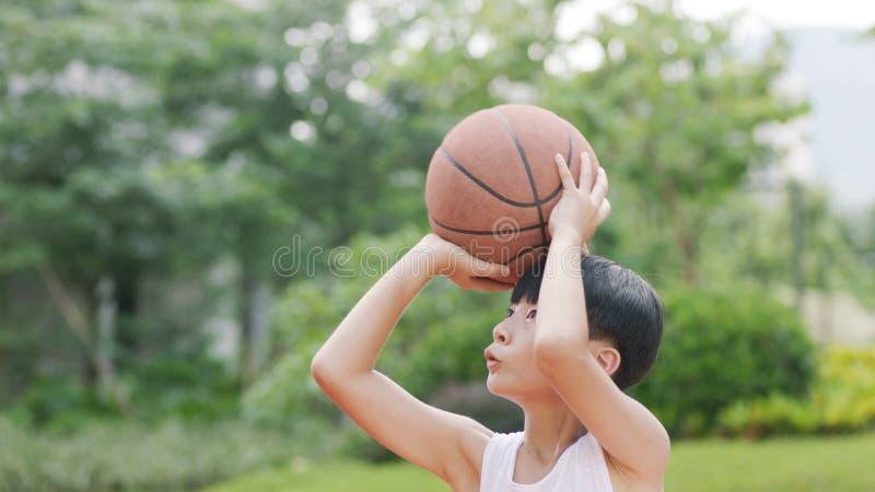 Nastoletnia Azjatycka chłopiec bawić się koszykówkę outdoors przygotowywa dla strzelać obrazy royalty free