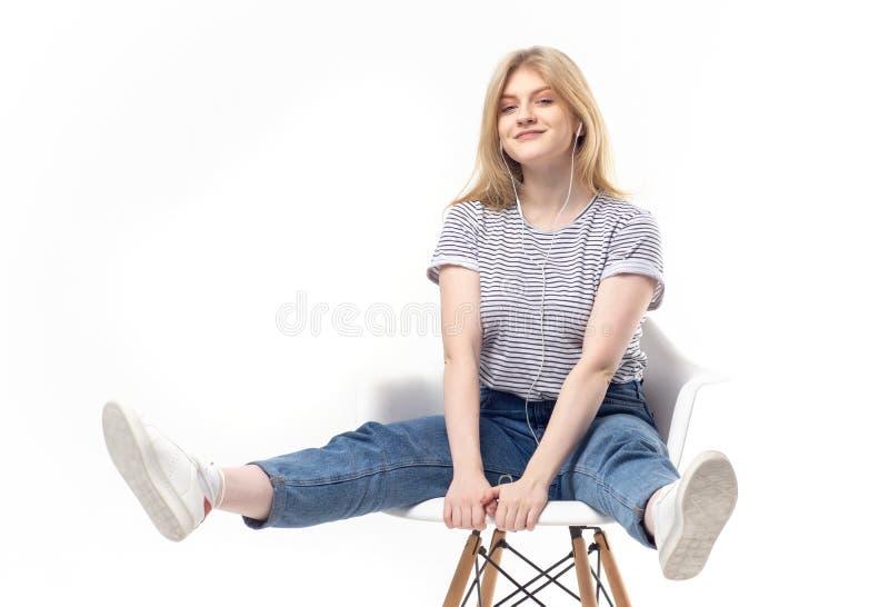 Nastoletnia blondynka w hełmofonach pozuje na krześle zdjęcie royalty free