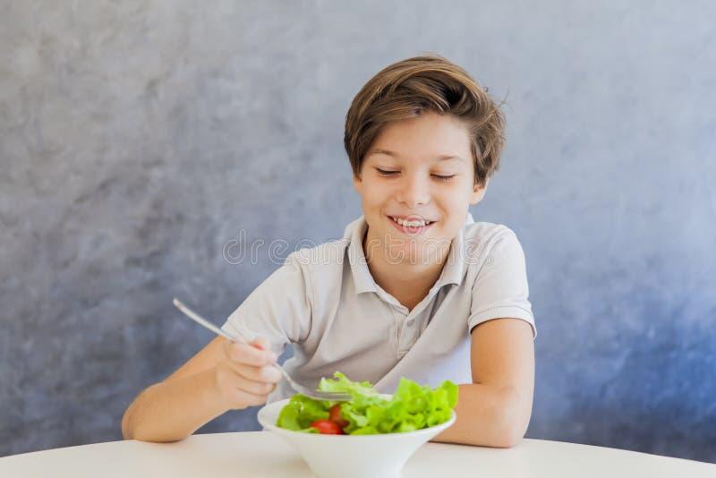 Nastoletnia chłopiec łasowania sałatka zdjęcie royalty free