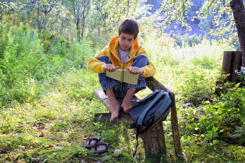 Nastoletnia chłopiec czyta książkę zdjęcie stock