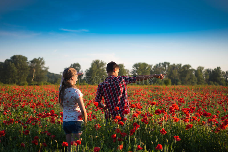 Nastoletnia chłopiec i dziewczyna pozuje na makowym polu fotografia stock