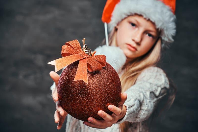 Nastoletnia chłopiec jest ubranym Santa kapelusz trzyma dużą Bożenarodzeniową piłkę na ciemnym textured tle zdjęcia royalty free