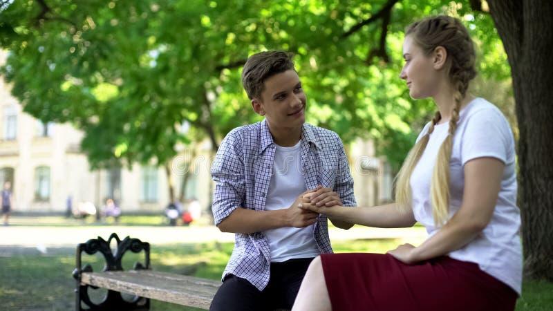 Nastoletnia chłopiec mienia dziewczyn ręka, patrzeje ona z miłością, romantyczni powiązania fotografia royalty free