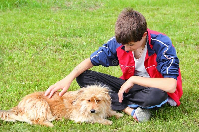 Nastoletnia chłopiec muska jego psiego zdjęcie stock