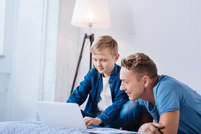 Nastoletnia chłopiec pokazuje jego prezentację ojciec zdjęcie royalty free