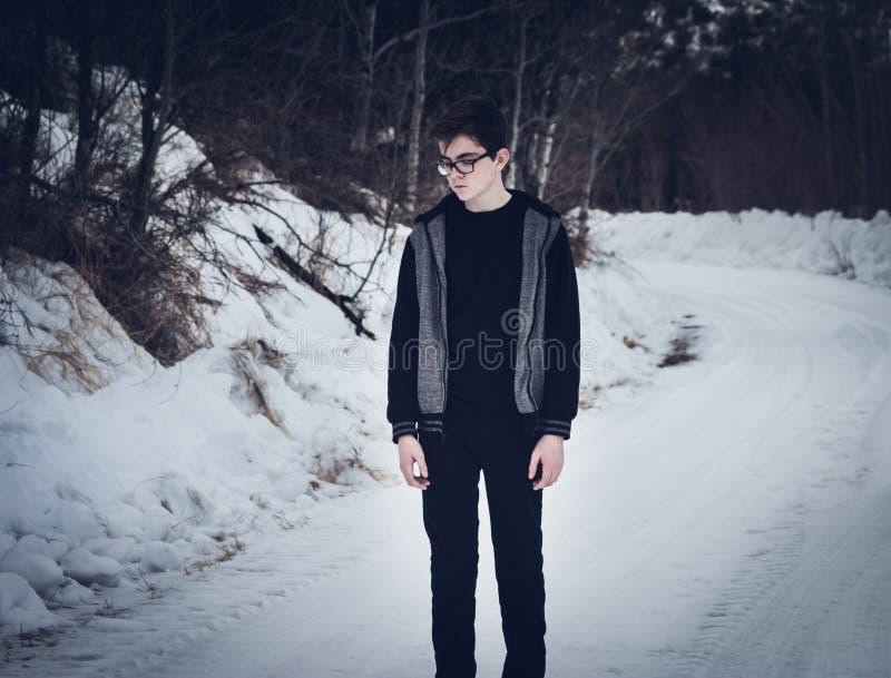 Nastoletnia chłopiec pozycja na śnieżystej drodze obraz royalty free