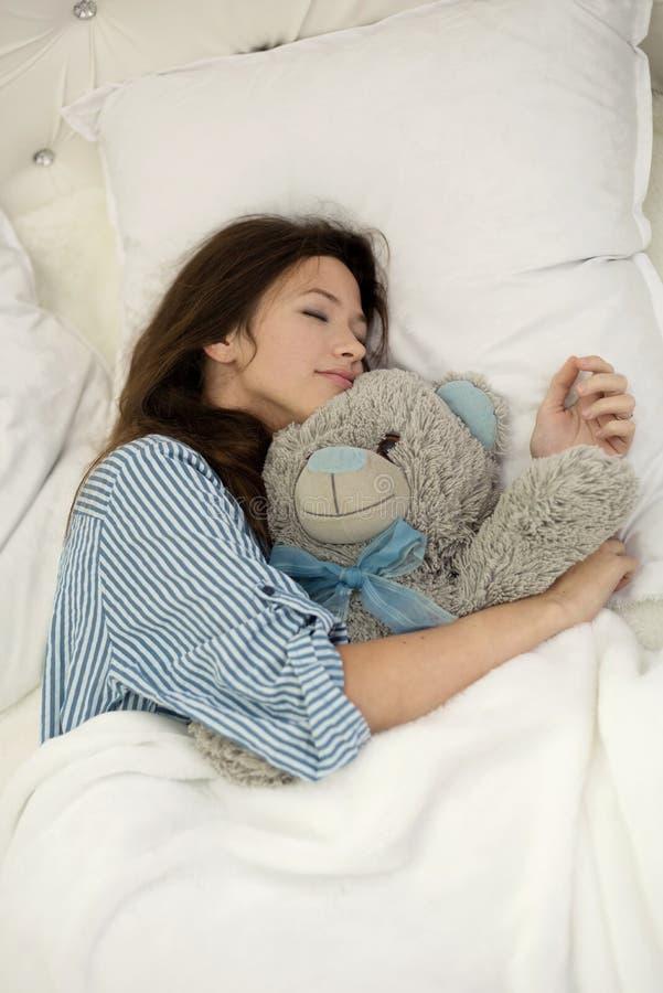 Nastoletnia dziewczyna śpiąca ściska misia podczas gdy obraz royalty free