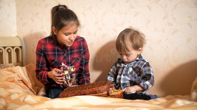 Nastoletnia dziewczyna bawić się z jej berbecia bratem na łóżku przy sypialnią obrazy royalty free
