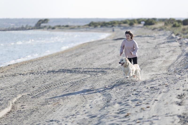Nastoletnia dziewczyna bawić się z jej psem na plaży fotografia royalty free