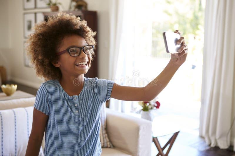 Nastoletnia dziewczyna bierze selfie fotografii pozycję w żywy izbowy śmiać się, zakończenie w górę, ostrość na przedpolu obraz royalty free