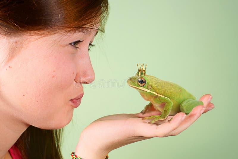 Nastoletnia dziewczyna całuje Drzewnej żaby Litoria infrafrenata z koroną na jego głowie obraz stock