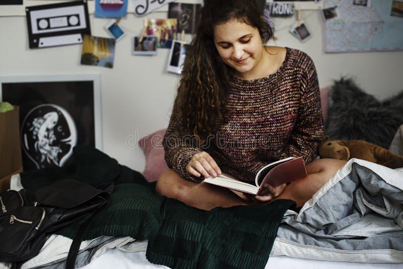 Nastoletnia dziewczyna czyta książkę w sypialni zdjęcia royalty free