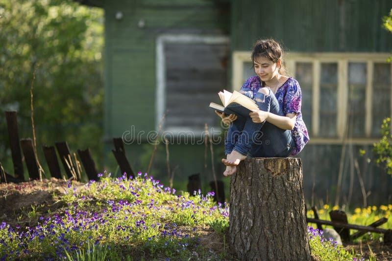 Nastoletnia dziewczyna czyta książkowego obsiadanie na fiszorku w jardzie obraz stock