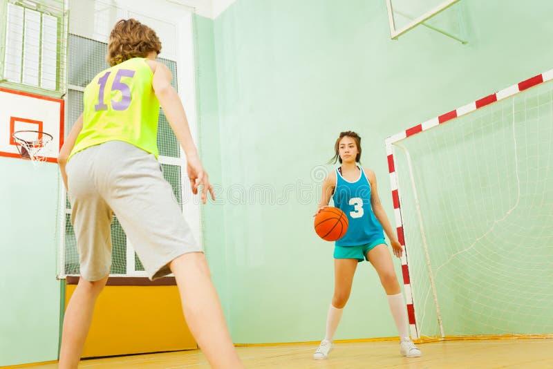 Nastoletnia dziewczyna drybluje koszykówkę podczas dopasowania obrazy royalty free