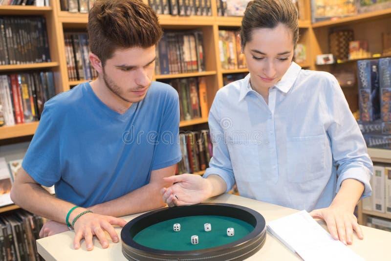 Nastoletnia dziewczyna i chłopiec bawić się kostka do gry fotografia stock
