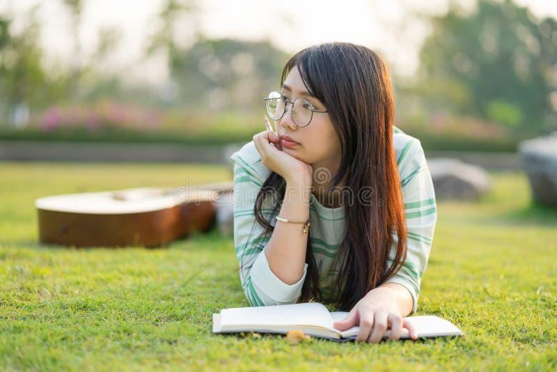 Nastoletnia dziewczyna jest ubranym szkło łgarskiego puszek z gitarą i książkami Na polu przy zmierzchem zdjęcia stock