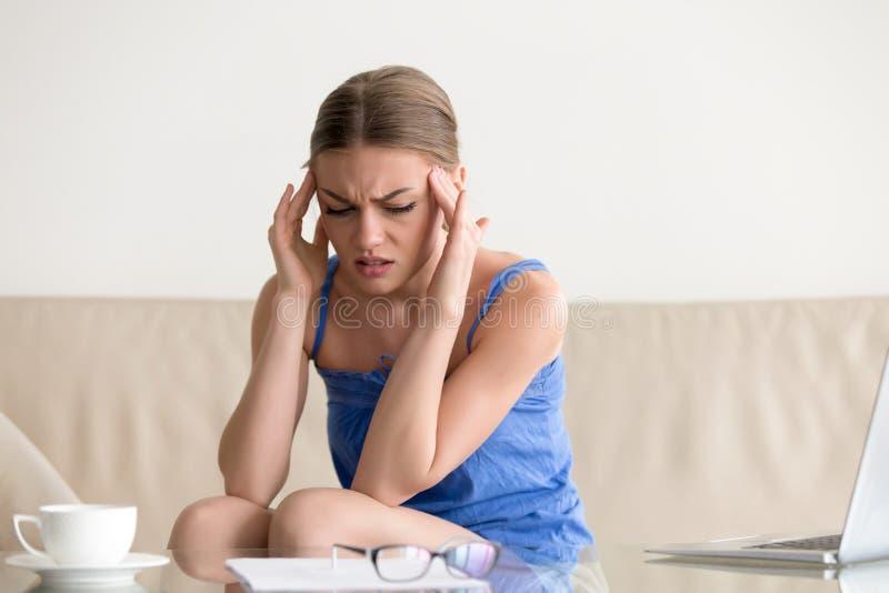 Nastoletnia dziewczyna ma ataka paniki, czujący oszołomioną migrenę, masuje zdjęcie stock