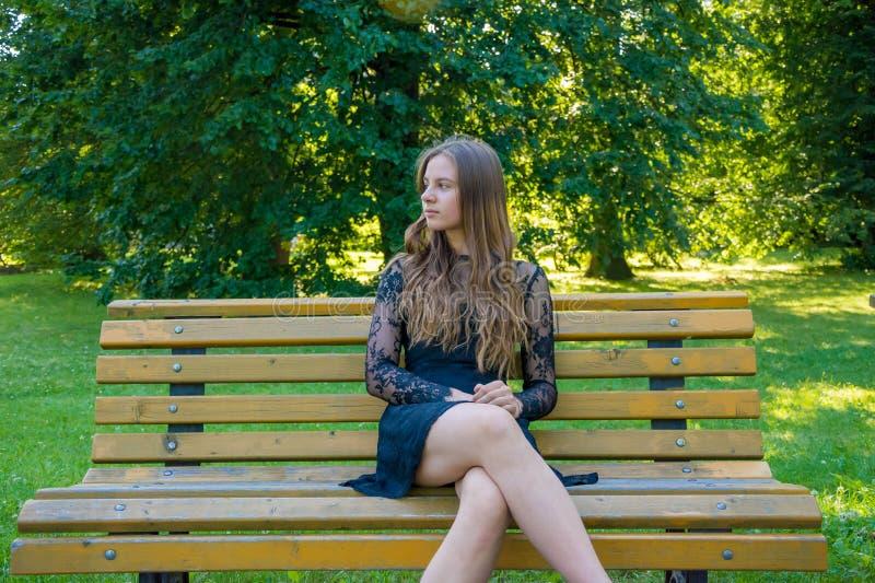 Nastoletnia dziewczyna na daktylowym czekania obsiadaniu na ławce w parku obrazy royalty free