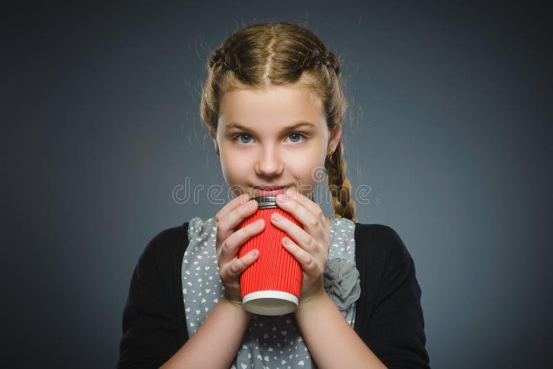 Nastoletnia dziewczyna napoju czerwona filiżanka kawy odizolowywająca na szarym tle obrazy stock