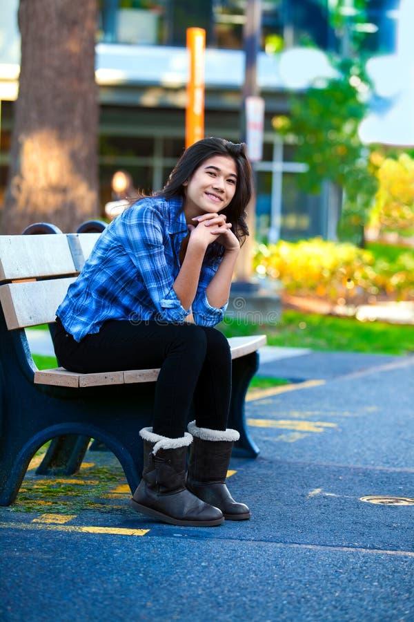 Nastoletnia dziewczyna odpoczywa na drewnianej ławce outdoors przy szkołą wyższa obraz royalty free