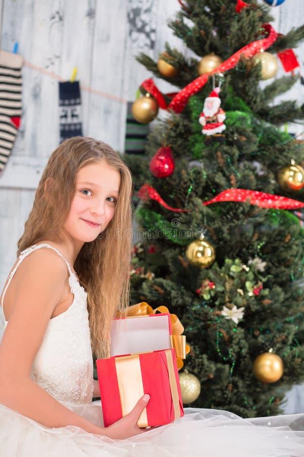 Nastoletnia dziewczyna otwiera pudełko Bożenarodzeniowa teraźniejszość blisko nowego roku drzewa obrazy stock