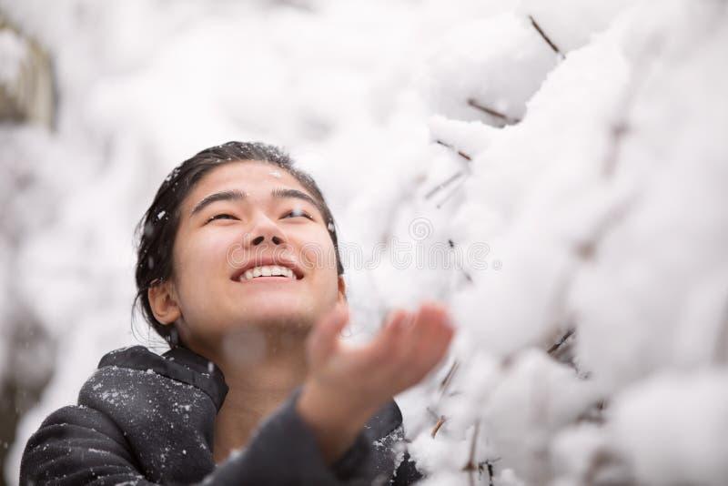 Nastoletnia dziewczyna outdoors zbroi szeroko rozpościerać cieszący się opad śniegu w zimie obraz stock
