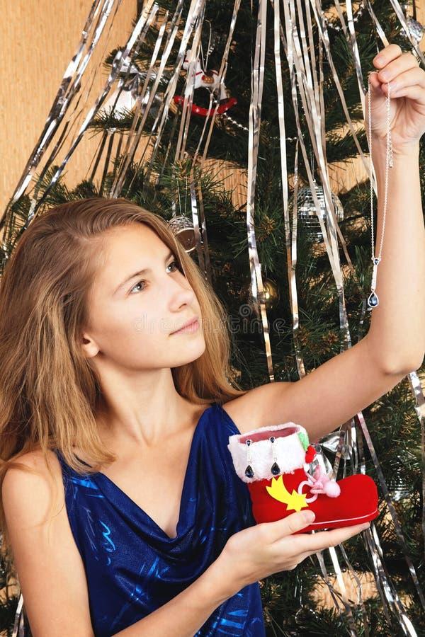 Nastoletnia dziewczyna patrzeje biżuterię w ręce, wyciąganej od Obuwianego Santa fotografia stock
