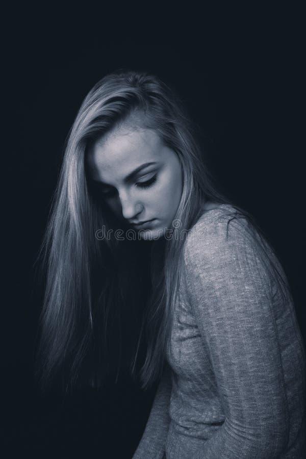 Nastoletnia dziewczyna patrzeje w dół z długim blondynem, siedzący w cieniach obrazy royalty free
