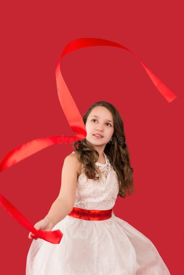 Nastoletnia dziewczyna podrzuca faborek, odizolowywającego na czerwieni zdjęcia stock