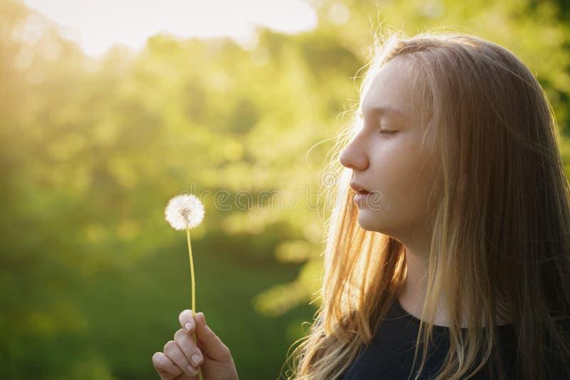 Nastoletnia dziewczyna przygotowywająca dmuchać dandelion fotografia stock