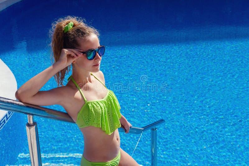 Nastoletnia dziewczyna relaksuje blisko pływackiego basenu obraz stock