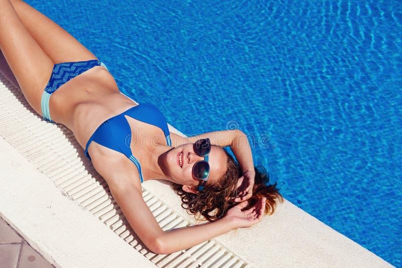 Nastoletnia dziewczyna relaksuje blisko pływackiego basenu fotografia stock
