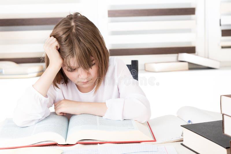 Nastoletnia dziewczyna robi jej pracie domowej, robi projektowi fotografia stock