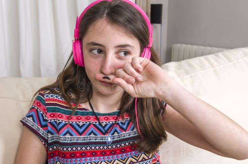 Nastoletnia dziewczyna robi wąsa gestowi z jej palcem na kanapie przy hom fotografia royalty free