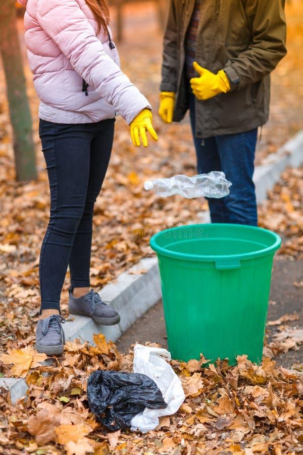 Nastoletnia dziewczyna rzuca plastikową butelkę w łzawicę i pokazuje ona aprobaty, jej tata stojaki obok ona obrazy royalty free