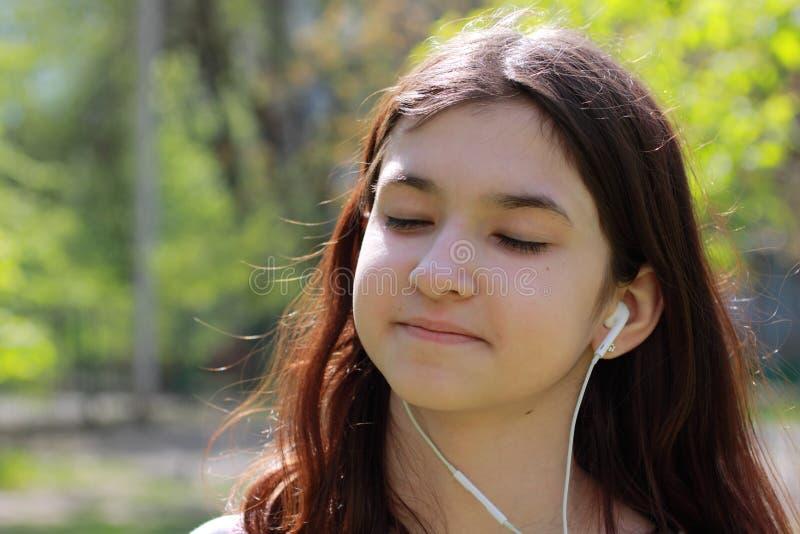 Nastoletnia dziewczyna słucha muzyka na hełmofonach od telefonu komórkowego zamkni?tej dziewczyny portret zamkni?ty Młoda dziewcz zdjęcie royalty free