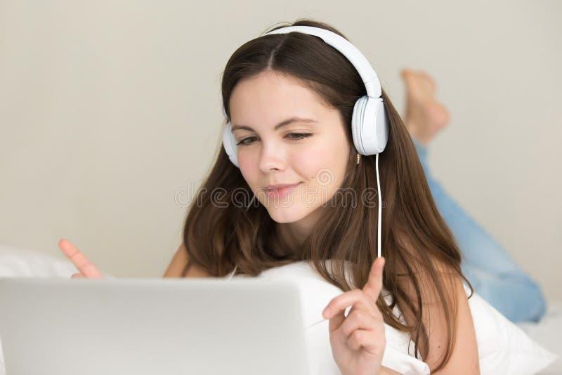Nastoletnia dziewczyna słucha wybierać piosenki online i kupować fotografia stock