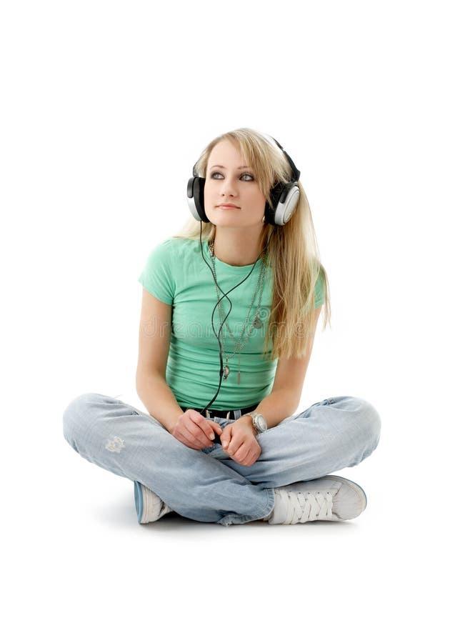 Nastoletnia dziewczyna siedzi na podłoga w hełmofonach obrazy royalty free