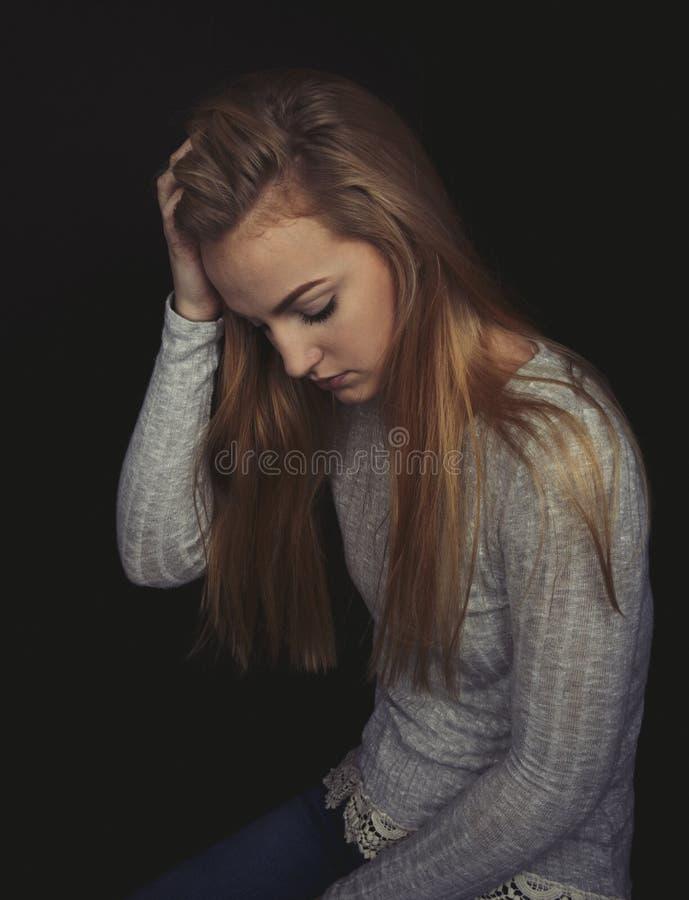 Nastoletnia dziewczyna siedzi patrzeć smutny z długim blondynem zdjęcia royalty free