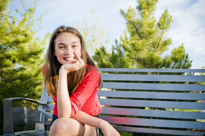 Nastoletnia dziewczyna siedzi uśmiechniętego outside fotografia royalty free