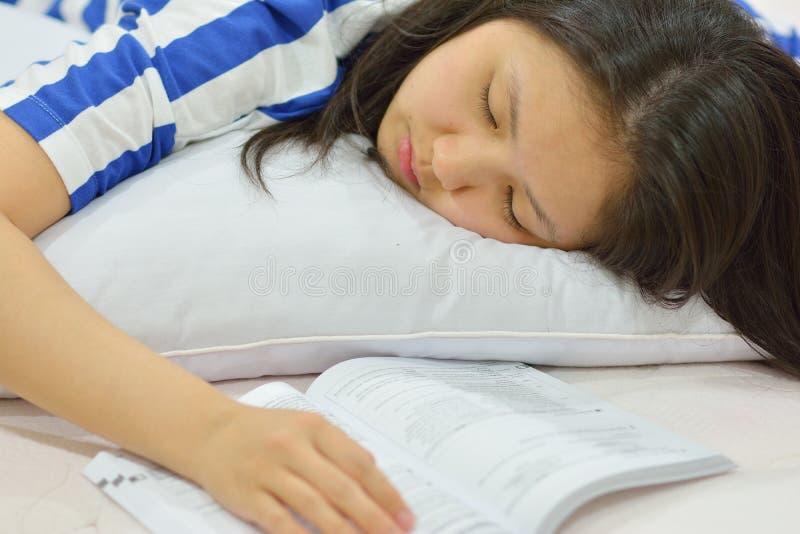 Nastoletnia dziewczyna spada uśpiony podczas gdy studiujący w łóżku zdjęcia stock